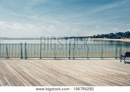 Empty ocean beach boardwalk pier at hot summer day against blue sky