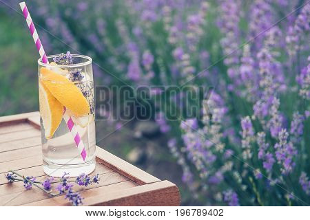 A glass of refreshing lemonade over a wooden chair. Blooming lavender flowers in the background.
