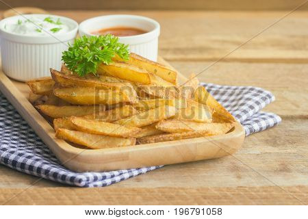 Homemade french fries serve with ketchup and sour cream or mayonnaise. Golden brown crispy french fries sprinkle with salt and oregano on wood plate for snack or appetizer. French fries on wood table with copy space for background.