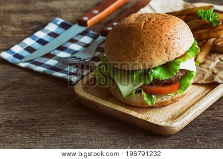 Homemade hamburger on wood plate with french fries. Delicious sandwich hamburger with meat or pork ham cheese and fresh vegetable. Hamburger or sandwich is the popular fast food for brunch or lunch. Sandwich in burger style on wood table.