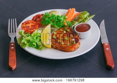 Barbecue pork steak on white plate served with barbecue sauce and vegetables. Pork steak for lunch or dinner on granite table. Moist and soft homemade pork barbecue with mash potato and vegetable. Pork barbecue or steak ready to served.
