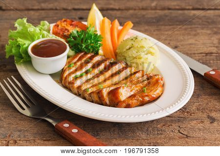 Barbecue pork steak slices on white plate. Delicious pork steak for lunch or dinner on wood table. Moist and soft homemade pork barbecue served with mash potato barbecue sauce and vegetable. Pork barbecue on wood table with copy space.