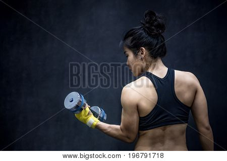Young Asian woman lifting dumbbell in weight training fitness gym sport exercise and muscular build helathy lifestyle