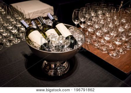 Sparkling wine bottles in ice bucket on wooden table surrounding with blurred champagne glasses background. Alcoholic beverage station for wedding after party at luxury hotel