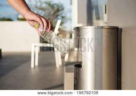Hand putting plastic bottle waste in garbage trash, recycle waste