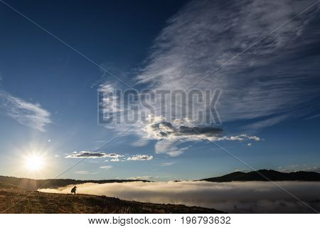 A photographer at dawn takes pictures of a beautiful thick mist over the lake from the top of the mountain