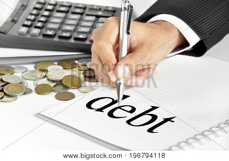 Hand with pen pointing to debt word on the paper - business and financial concepts