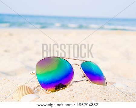 sunglasses on the beach with shell and sea backround Concept of summer traveling