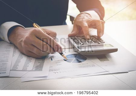Businessman Pen Pointing Graph Chart While Using A Calculator To Calculate The Numbers. Accounting ,