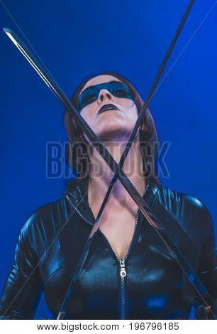Agent, Brunette girl dressed in leather and latex fitted with japanese swords on blue background