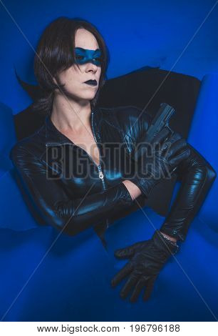 Detective, Brunette girl dressed in leather and latex fitted with pistol on blue background