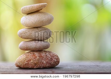 Balance Stone on wooden floor and soft sunlight in the garden concept of meditation and spa.