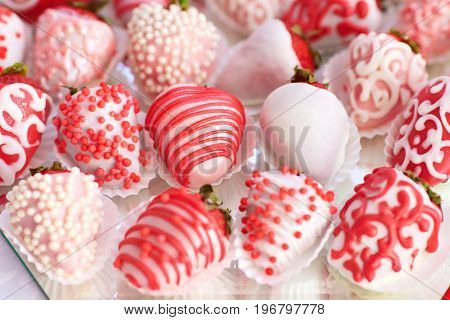 Strawberries covered in white chocolate and decorated with pink glaze