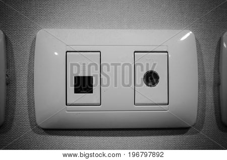 Satellite and modular outlet plates on black and white tone.