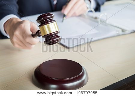 Male Judge In A Courtroom Striking The Gavel On Sounding Block