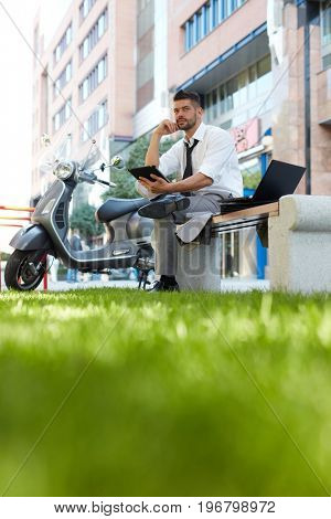 Businessman outdoors working with mobile devices sitting on brench in front of business building.