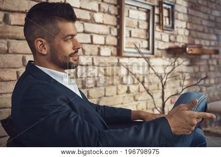 Profile of goodlooking young businessman front of brick wall.