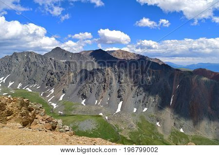 View of black mountain ridge snow and ravine with green grass. Altai mountains. Aktash Altay Republic Russia.