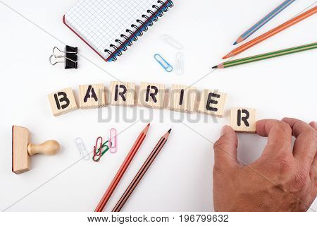 Barrier concept. Wooden letters on a white background.