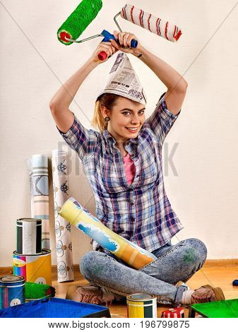 Repair home woman holding paint roller for wallpaper. Smiling girl in newspaper cap renovation apartment . Female took loan for repairs and is very happy idea.