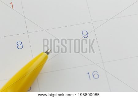 yellow pen points to the number 9 on calendar background in concept of appointment schedules and important dates.