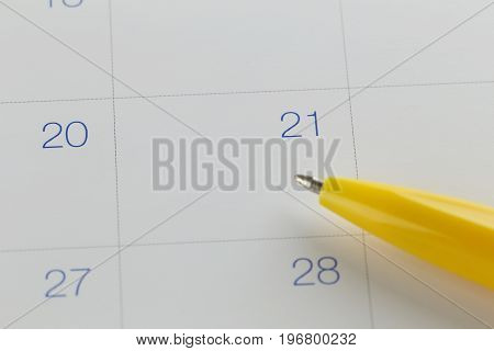yellow pen points to the number 21 on calendar background in concept of appointment schedules and important dates.