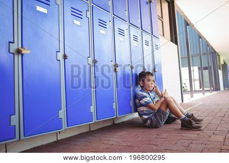 Side view of boy talking on mobile phone while sitting by lockers in corridor at school