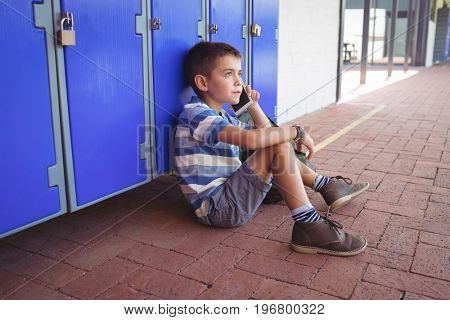 High angle view of boy talking on mobile phone while sitting by lockers in corridor at school