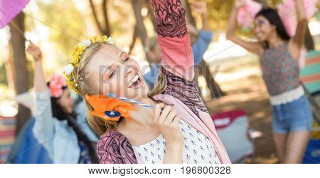 Happy woman holding pinwheel while enjoying at campsite