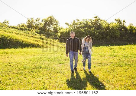 Pregnant woman with husband walking in nature.