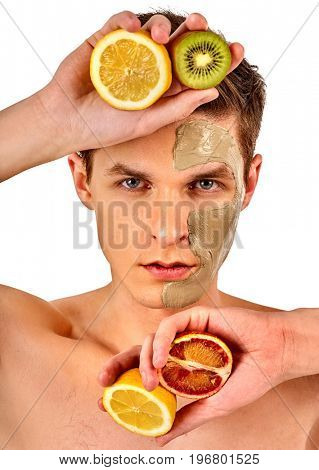 Facial mask from fresh fruits and clay for man concept. Face with treatment mud applied. Male holding lemon half for skin care procedure in salon. Cosmetic masks with natural ingredients.