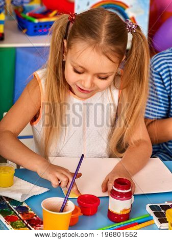 Small student girl painting in art school class. Child drawing by paints on table. Craft drawing education develops creative abilities of children. Preparing for a children's art exhibition.