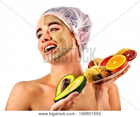 Avocado clay face mask. Woman in medical hat holding half of green fruit. Facial beautiful procedure concept. Masks for skin created from natural ingredient. Girl finally got rid of skin defects.