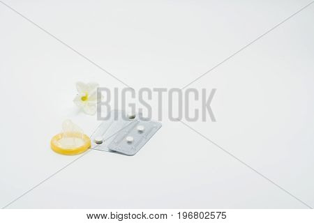 Two blister pack of emergency contraceptive pills condom and flower on white background
