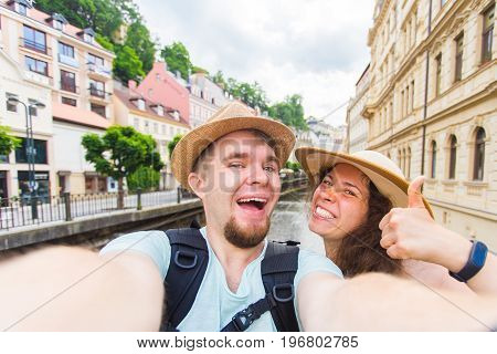 Happy couple, attractive woman and man walking in city and enjoying romance. Lovers making selfie and smiling. Tourists having fun together. Prague , Czech Republic.