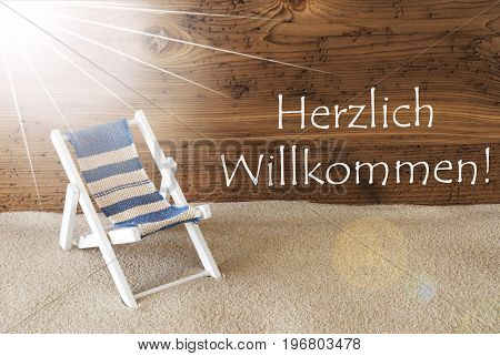 Sunny Summer Greeting Card With Sand And Aged Wooden Background. German Text Willkommen Means Welcome. Deck Chair For Holiday Or Vacation Feeling.