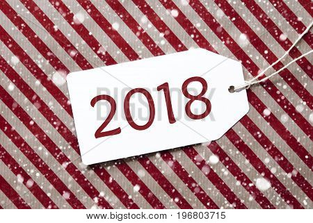 One Label On A Red And Brown Striped Wrapping Paper. Textured Background With Snowflakes. Tag With Ribbon. English Text 2018 For Happy New Years Greeting