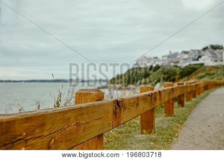 Walk along the waterfront of the coastal town. Wooden fence on the background of the sea with the city. blurred background. Copy space for your text