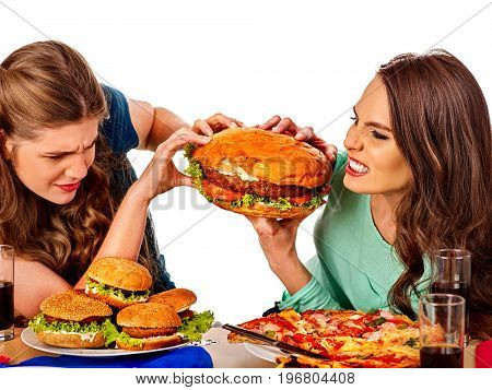 Women eating fast food. Gils eat hamburger with ham. Girlfriends jokingly fight for a huge hamburger on white background isolated. People try to feed each other.