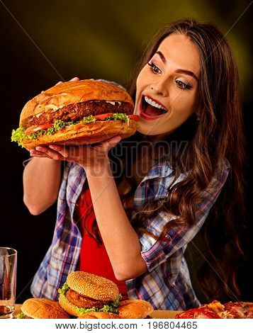 Woman eating hamburger. Student consume fast food. Girl bite of very big burger . Girl trying to eat a lot of junk. Advertise fast food on black background. Supper of busy person idea.