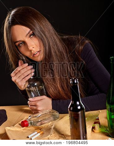 Woman alcoholism is social problem. Female drinking is cause of nervous stress . She with green alcohol bottle in bad mood. Drunken woman sadly looks camera. Unhappy love concept.