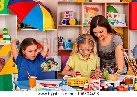 Kids playroom organization of children painting and drawing in kid's club. Craft lesson in primary school. Kindergarten teacher and small students work together. Girls at drawing lesson.