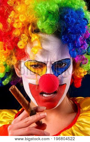 Evil clown on black background. Mad woman is smoking cigar. Portrait of crazy female with an angry look after performance. Female hates children idea.
