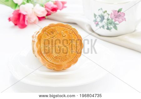 Moon cakes of swan design over white plates to celebrate Chinese moon festival on white table with tea pot and beautiful flowers