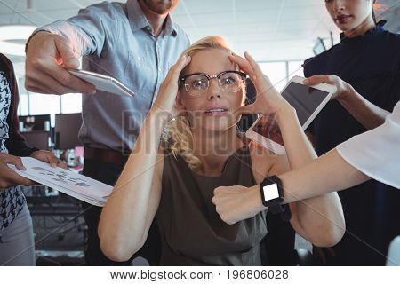 Frustrated businesswoman amidst team holding technologies at office
