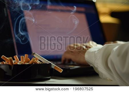 Man working on laptop computer with lit and smoking cigarette on an ashtray filled with cigarette butts