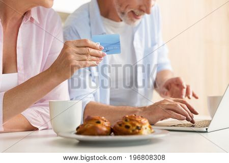 Cropped photo of mature loving couple family standing at the kitchen using laptop computer holding credit card