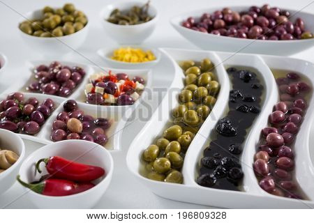 Close-up of marinated olives and vegetables on white background