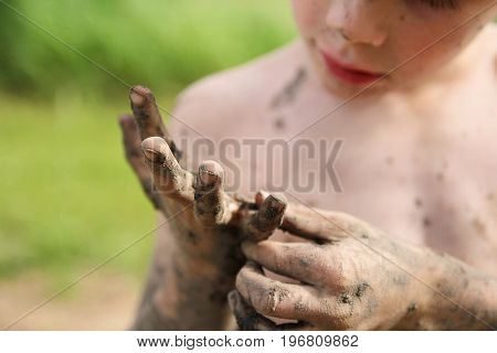 A little boy who has been playing outside in the summer is picking mud off of his very dirty hands. Shallow depth of field.
