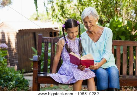 Smiling grandmother reading book to granddaughter while sitting on wooden bench at backyard